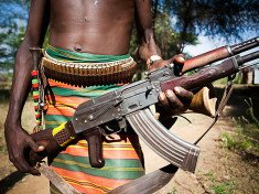 HAMER VILLAGE, OMO VALLEY, ETHIOPIA. An Ethiopian man holds a kalashnikov rifle at his waist.